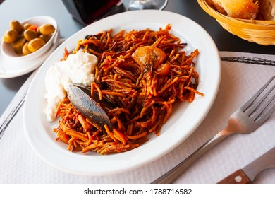 Traditional Catalan pasta paella (fideua) with shrimps and mussels served with piquante aioli sauce