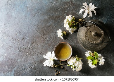 Traditional ceramic cup of hot green tea with black iron teapot, spring flowers white magnolia and cherry blooming branches over dark blue texture background. Top view, copy space.