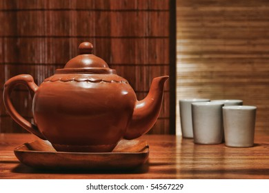 Traditional ceramic teapot and teacups in an Asian inspired theme
