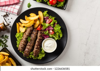 Traditional cevapcici served with baked potatoes. Flat lay. Stone background. Top view.