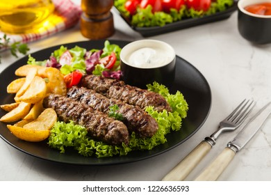 Traditional cevapcici served with baked potatoes. Stone background. Front view.