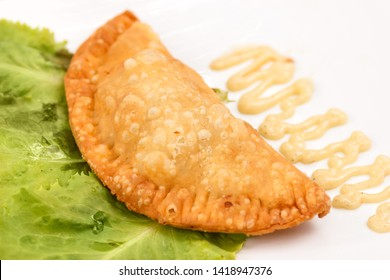 Traditional cheburek pie (meat in dough fried in hot oil) on plate with sauce and salad leaf