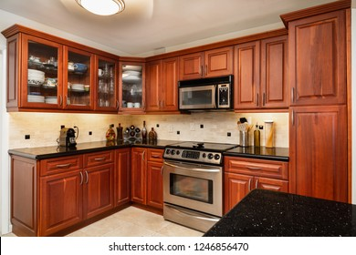 Traditional cherry wood cabinet home kitchen with a black granite countertop.