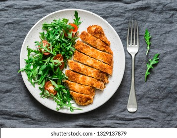 Traditional chicken schnitzel with arugula cherry tomatoes salad on grey background, top view
