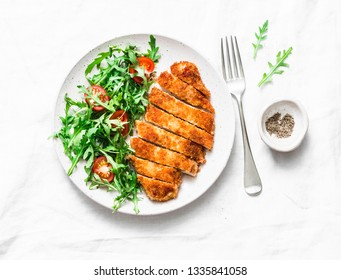 Traditional chicken schnitzel with arugula cherry tomatoes salad on light background, top view