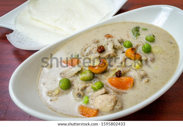 Traditional Chicken Stew in Kerala Style with cashew and vegetables along with Appams.