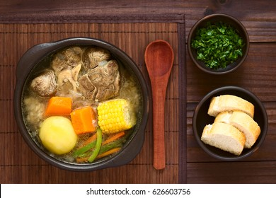 Traditional Chilean Cazuela de Vacuno or Carne beef soup with potato, corn, pumpkin, carrot, bell pepper, onion and rice, parsley and bread on the side, photographed overhead with natural light