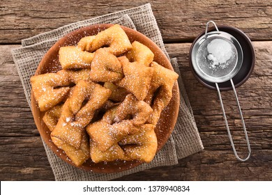 Traditional Chilean sweet calzones rotos deep-fried pastries sprinkled with powdered sugar served on wooden plate, photographed overhead