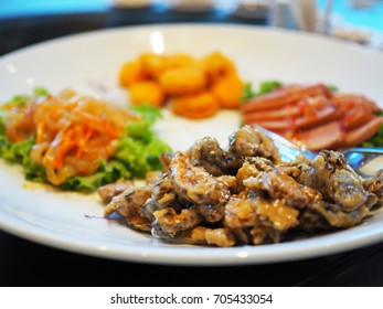 Traditional Chinese banquet food: deep fried black Shiitake mushrooms with blurred cut roasted duck, shellfish, and cold jellyfish served on wide white ceramic plate as Chinese banquet horderves