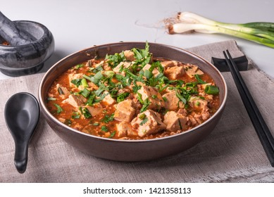 Traditional Chinese dish Mapo tofu with minced meat and tofu cheese in a bowl on a linen rustic napkin