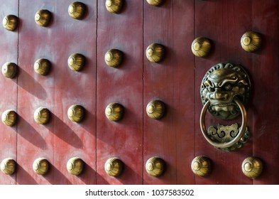 Traditional Chinese doors with brass lion head door knockers and ornamental studs. The number of studs represent status of the owner.