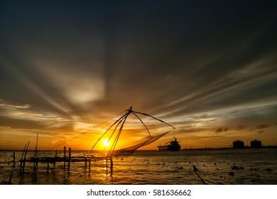 Traditional Chinese fishing net in Kochi, Kerala, India, during sunset.