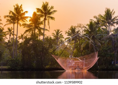 A traditional Chinese fishing net is raised in the sunset on a lake, Backwaters, Kerala state, India.