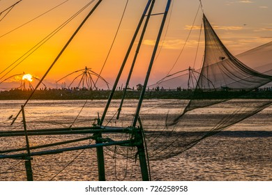 Traditional Chinese fishing nets line the banks of the Periyar river in India at sunset