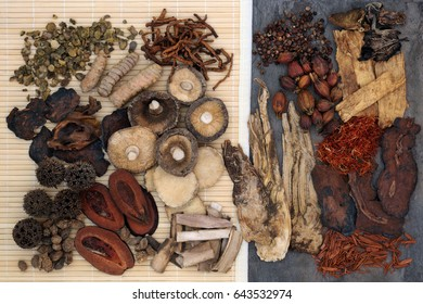 Traditional chinese herb selection used in herbal medicine on bamboo and marble.