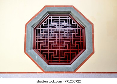Traditional Chinese hexagonal window with traditional geometric grill set in a temple wall