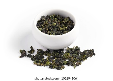 Traditional Chinese Oolong tea in cup and near, on white background. Tie Guan Yin
