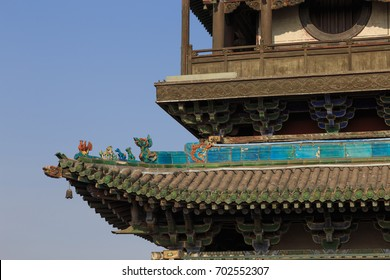 Traditional chinese roof. Details of a roof at a tower in the ancient City of Ping Yao (UNESCO World Heritage site). A famous historical site in Pingyao, Shanxi, China.