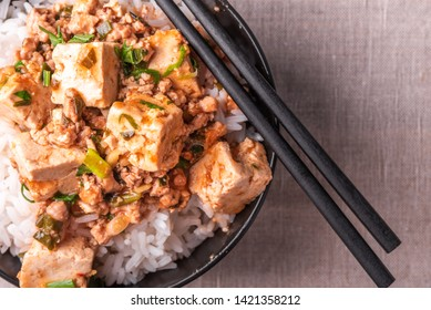 Traditional Chinese Sichuan cuisine - a bowl of rice with mapo tofu on a rustic background
