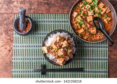 Traditional Chinese Sichuan cuisine - a bowl of rice with mapo tofu and a plate of mapo doufu on a bamboo napkin and a wooden rustic background