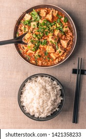 Traditional Chinese Sichuan cuisine - a bowl of rice and mapo tofu in a large plate on a rustic table