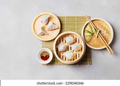 Traditional chinese steamed dumplings Dim Sums in bamboo steamer with sauce and chopsticks on light surface with copy space. Flat lay composition Asian food background.