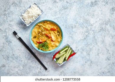 Traditional Chinese or Thai chicken yellow curry with vegetables served with steamed rice cucomber and hot chilli pepper on side. Top view with copy space on stone background.