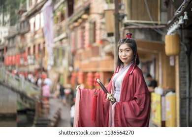 Traditional Chinese warrior, commander costume with sword, Asian beautiful girl. In background of Fenghuang the famous ancient town in China. Culture, Portrait.