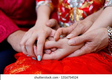 Traditional Chinese wedding. Mother and father holding hands of daughter-young bride at her wedding day.