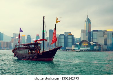 Traditional Chinese wooden sailing ship with red sails in Victoria harbor. Hong Kong.