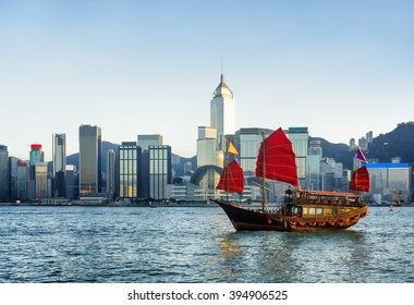 Traditional Chinese wooden sailing ship with red sails in Victoria harbor in rays of setting sun. Skyscrapers in downtown of Hong Kong are visible from Kowloon side. The Hong Kong Island skyline.