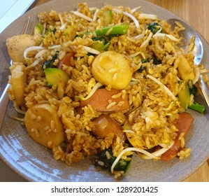 Traditional Chinese-Indonesian fried rice; with fishball, beef sausage, bean sprouts, bok choy, shredded chicken, and egg; on top of a circular plate, with spoon and fork.
