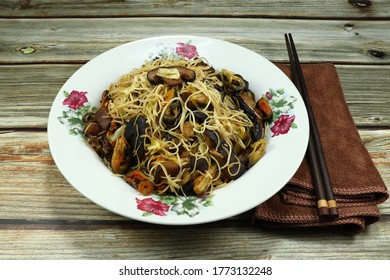 Traditional Chinese-styled fried noodle (Haphazardly stir fried) with mushroom, shrimp and mussel meat on the plate. Famous noodle menu with seafood in Asia restaurant.