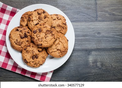 Traditional chocolate chip cookies on rustic wooden table. Space for text. View top.