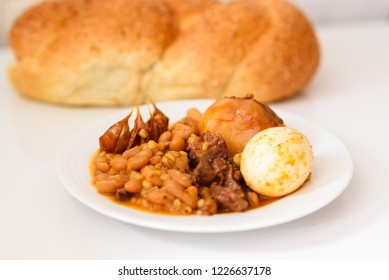 Traditional Cholent (Hamin) special Slow Cooked Stew in Jewish cuisine the main dish for the Shabbat meal made with beef, potato, beans, barley, eggs and more and served with challah bread for Sabbath