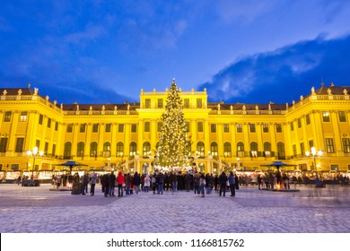 Traditional Christkindlmarkt christmas market in Vienna with illuminated Schönbrunn palace. Tourists in festive mood gather around fairy lights decorated Christmas tree at dusk in Advent.
