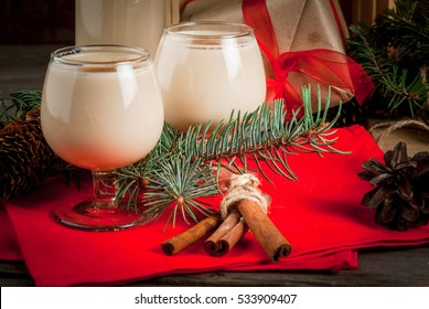 Traditional Christmas alcoholic cocktail - Irish Cream, Cola de mono (monkey tail), decorated with cinnamon. Against the background of Christmas decorations on a wooden table. Copy space