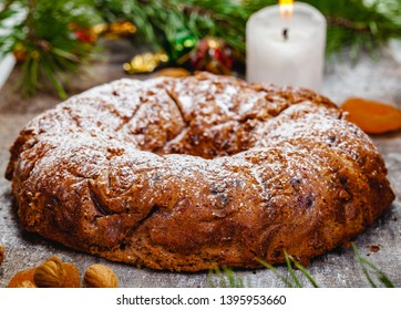 Traditional Christmas cake with dried fruits, raisins and nuts with Christmas decorations on wooden background. Close up