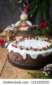 Traditional Christmas cake with fruits, nuts and white glaze with Christmas decorations