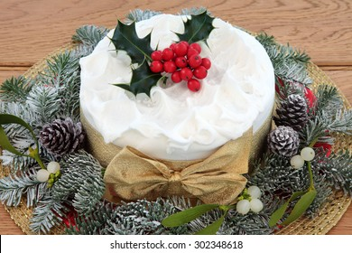 Traditional christmas cake with holly, mistletoe and winter greenery over oak background.
