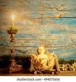 Traditional Christmas card, Baby Jesus in his crib and vintage candle in rustic wooden background with blank