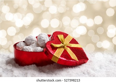 Traditional Christmas cookies with almonds in heart shape gift box on snow