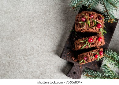 Traditional Christmas dessert, Christmas yule log cake with chocolate cream, cranberry and rosemary twigs. On stone gray background with Christmas tree branches, copy space top view