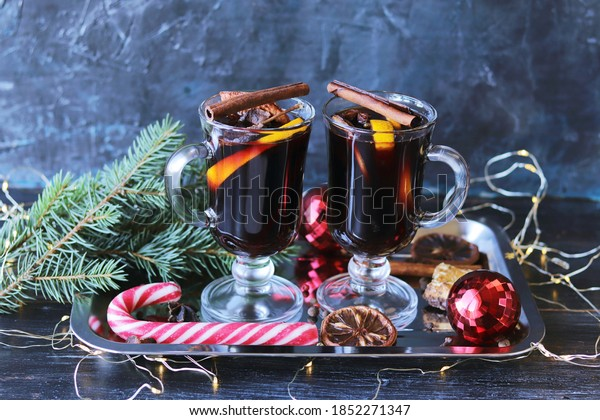 Traditional Christmas drink, cups with mulled wine, spices, fir branches, Christmas toys and illumination on a dark background, celebration concept, home comfort, winter