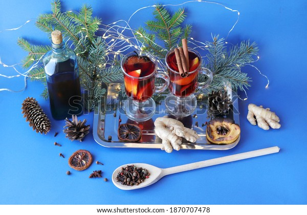 Traditional Christmas drink, cups with mulled wine, spices, fir branches and illumination on a dark background, the concept of home comfort, winter holidays celebration