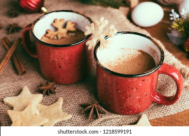 Traditional Christmas drink eggnog with cinnamon, anise stars and grated nutmeg in red mugs on the wooden table. Gingerbreads, eggs, and fir-tree decoration