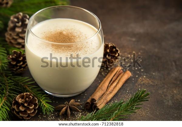 Traditional Christmas drink eggnog with grated nutmeg  and cinnamon. Selective focus.