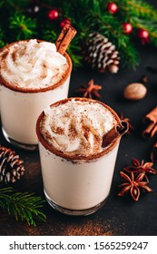 Traditional Christmas drink Eggnog with whipped cream and cinnamon on dark stone background. Hot beverage for winter holidays.