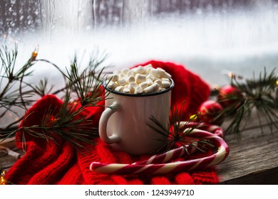 Traditional Christmas drinks. North Pole Cocktail with candy cane sweets peppermint hot chocolate or cocoa ginger ad milk near the window. decoration copy space
