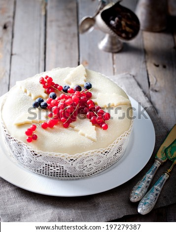 Traditional Christmas Fruit Cake pudding with marzipan and fresh berries on a wooden background
